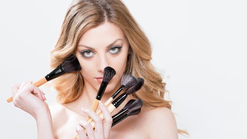 Mujer hermosa con los cepillos del maquillaje fotografía de archivo libre de regalías