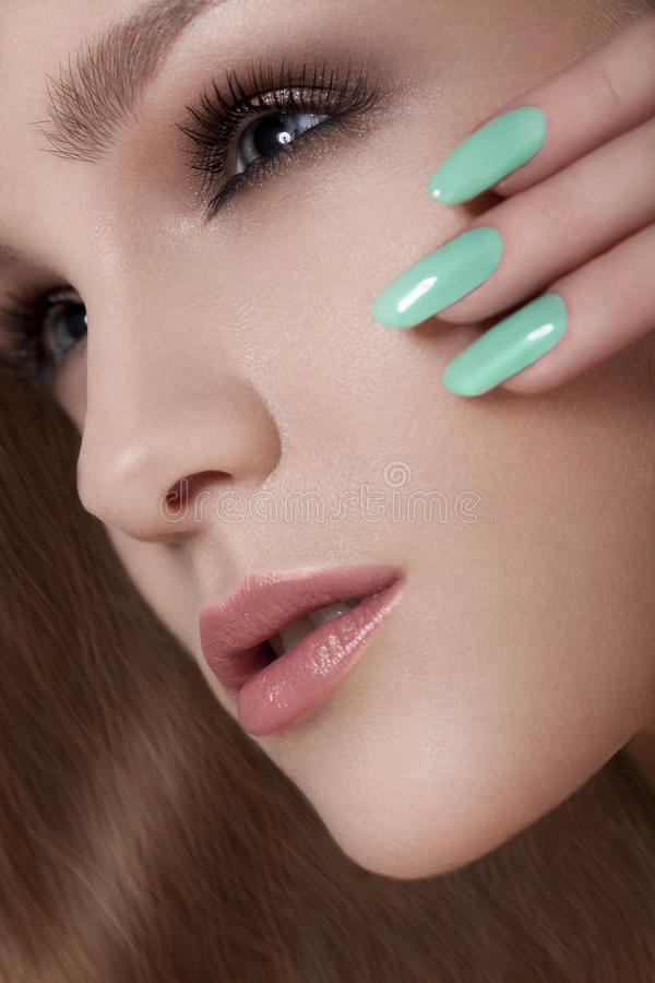 Mujer hermosa con los clavos coloridos y el maquillaje de lujo. Cara hermosa de la muchacha fotografía de archivo libre de regalías