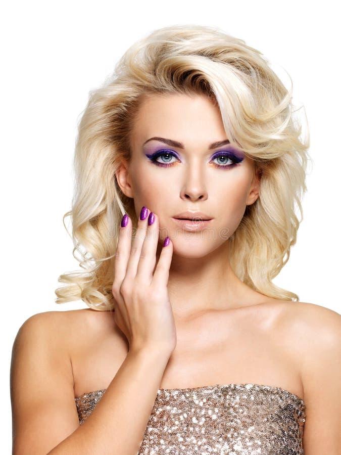 Mujer hermosa con los clavos de la púrpura de la belleza imagenes de archivo