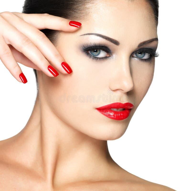 Mujer hermosa con los clavos rojos y el maquillaje de la manera fotografía de archivo libre de regalías