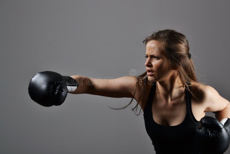 Mujer hermosa con los guantes de boxeo negros fotografía de archivo libre de regalías