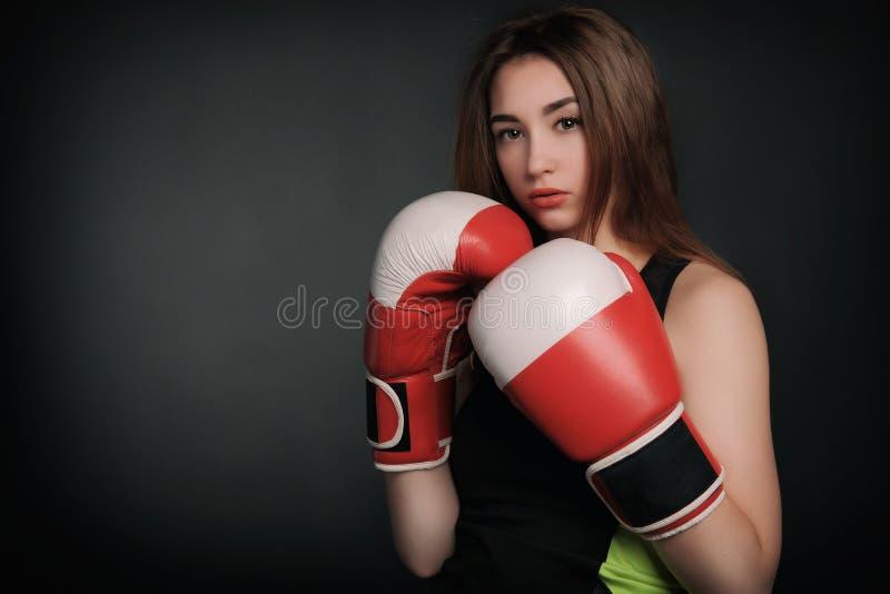 Mujer hermosa con los guantes de boxeo rojos, fondo negro foto de archivo libre de regalías