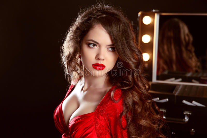 Mujer hermosa con los labios atractivos en el vestido rojo que presenta en el vestido de r foto de archivo