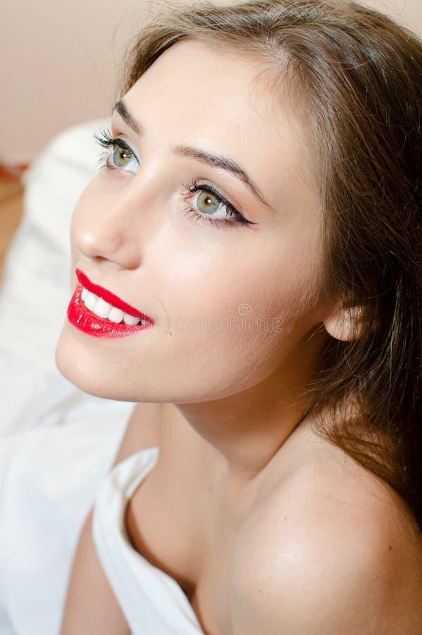 Mujer hermosa con los labios rojos de los ojos verdes que miran para arriba sonrientes en cama fotografía de archivo libre de regalías
