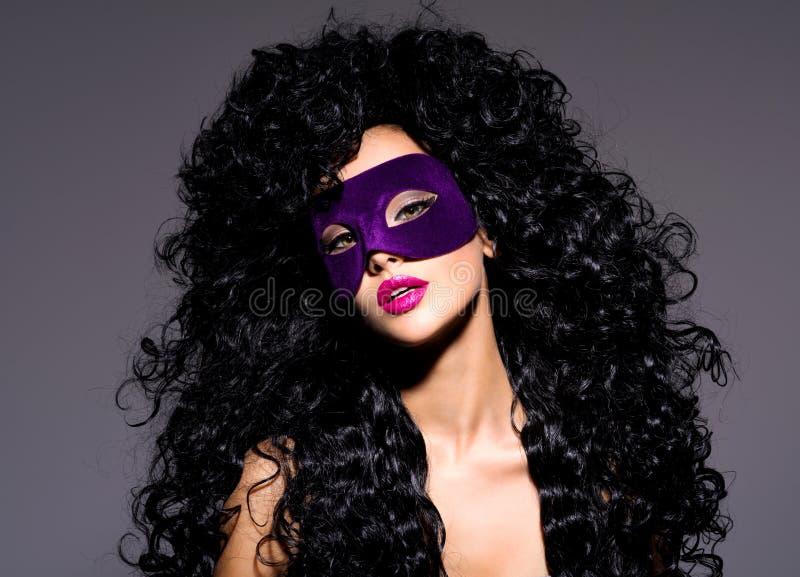 Mujer hermosa con los pelos negros y máscara violeta del teatro en fac imagen de archivo