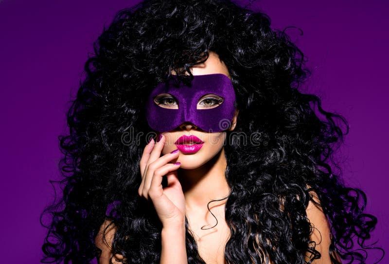 Mujer hermosa con los pelos negros y máscara violeta del teatro en fac imagen de archivo libre de regalías