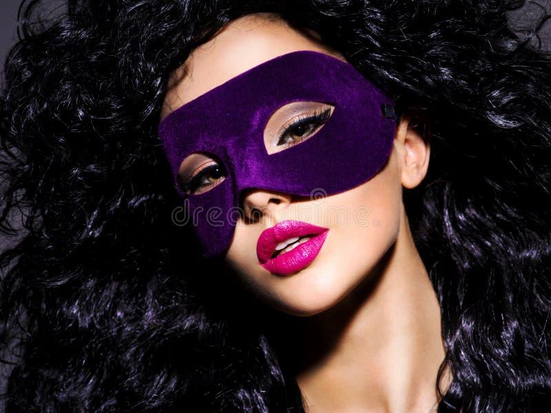 Mujer hermosa con los pelos negros y máscara violeta del teatro en fac foto de archivo