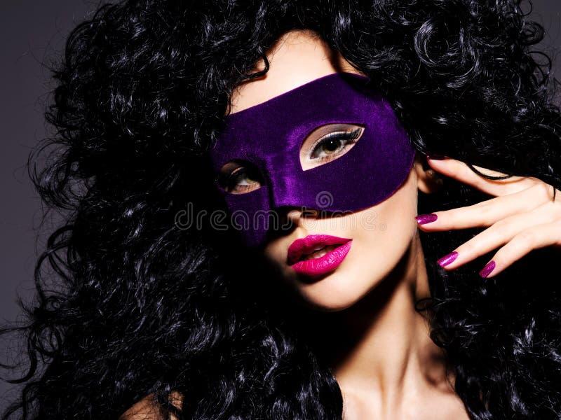 Mujer hermosa con los pelos negros y máscara violeta del teatro en fac fotos de archivo