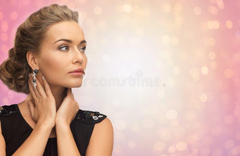 Mujer hermosa con los pendientes del diamante imagen de archivo