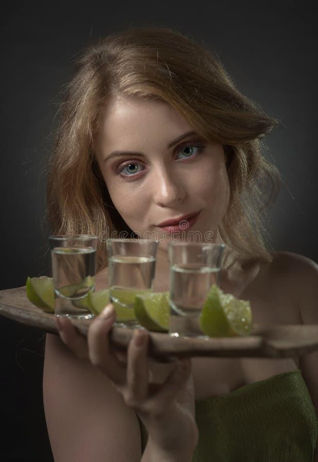 Mujer hermosa con los vidrios de rebanadas del tequila y de la cal imágenes de archivo libres de regalías