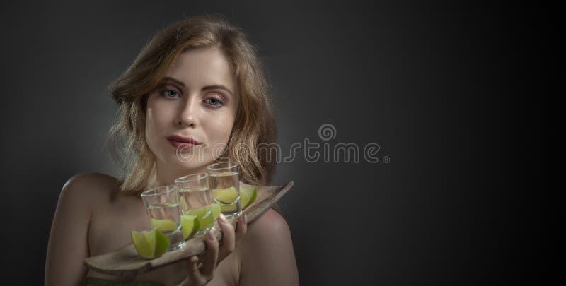 Mujer hermosa con los vidrios de rebanadas del tequila y de la cal foto de archivo