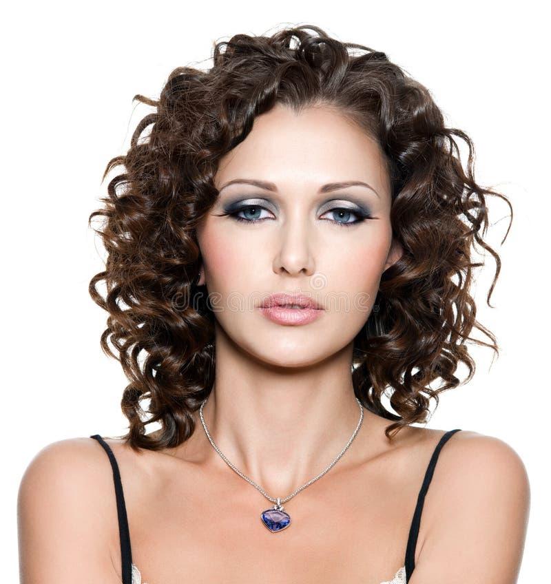 Mujer hermosa con maquillaje de la manera y pelo rizado fotografía de archivo