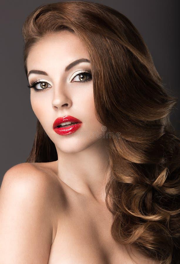 Mujer hermosa con maquillaje de la tarde, labios rojos y rizos Cara de la belleza imágenes de archivo libres de regalías
