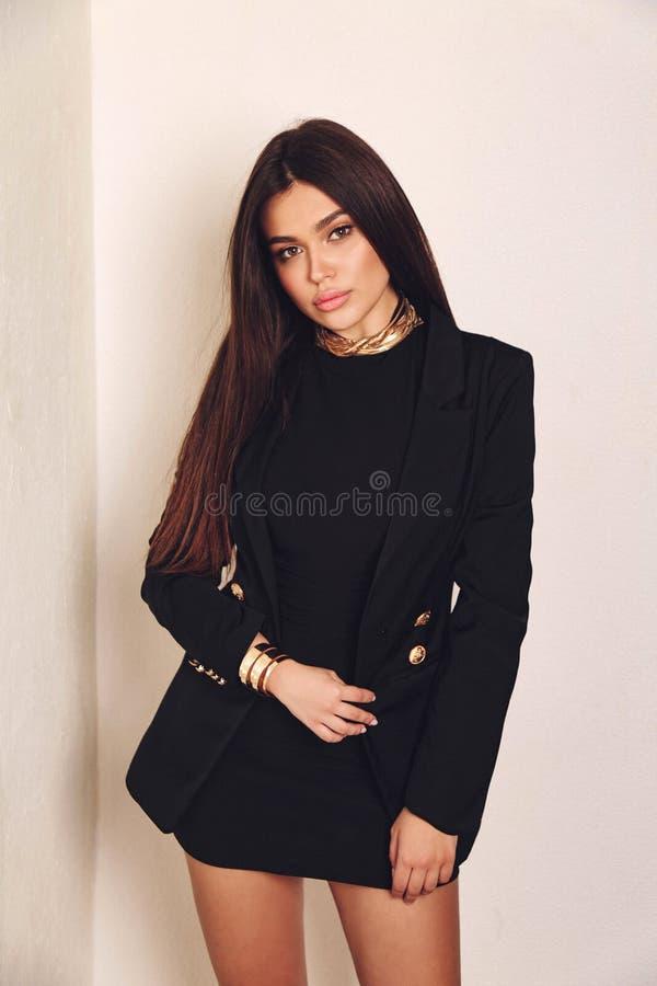 Mujer hermosa con pelo oscuro en vestido elegante con accesorios fotografía de archivo