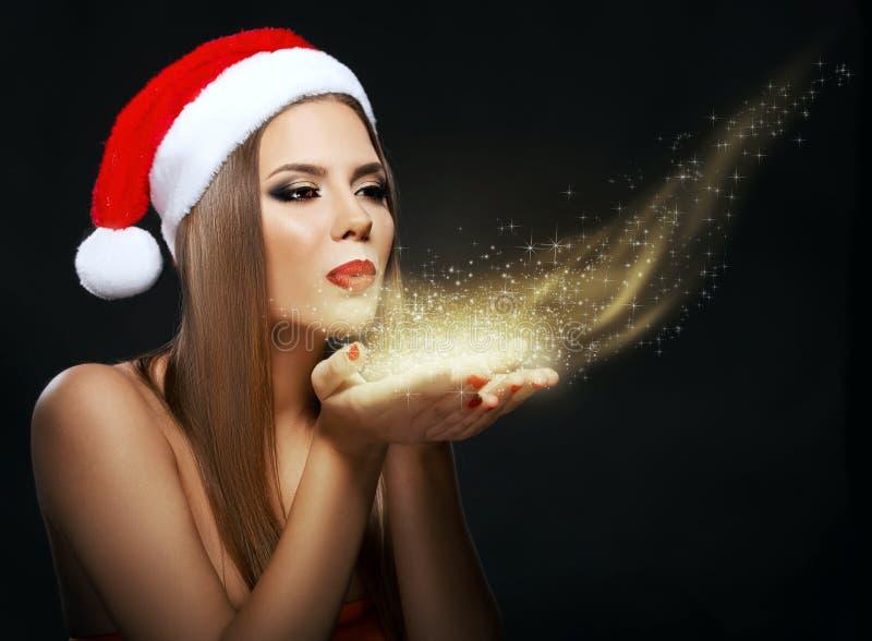 Mujer hermosa con Santa& x27; sombrero de s, polvo de oro que sopla imagen de archivo
