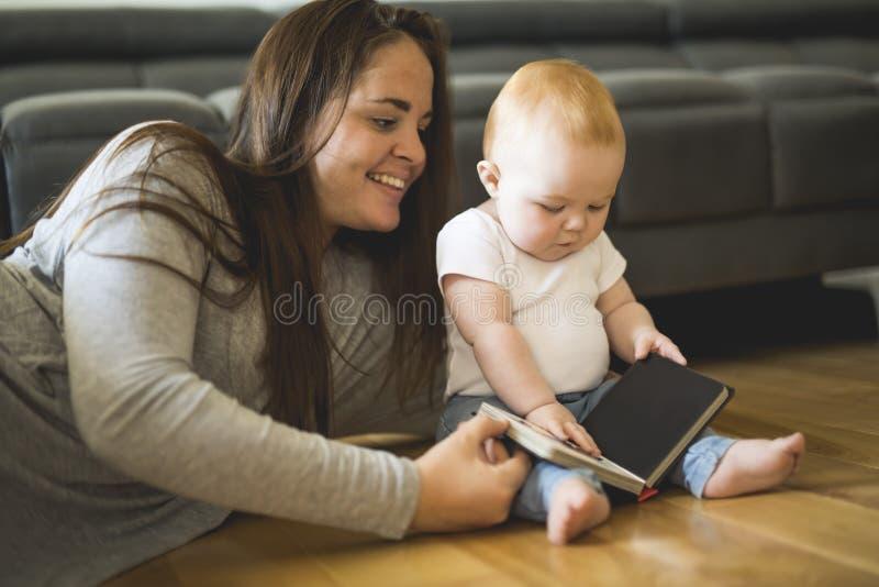 Mujer hermosa con su bebé y un libro en la sala de estar imágenes de archivo libres de regalías