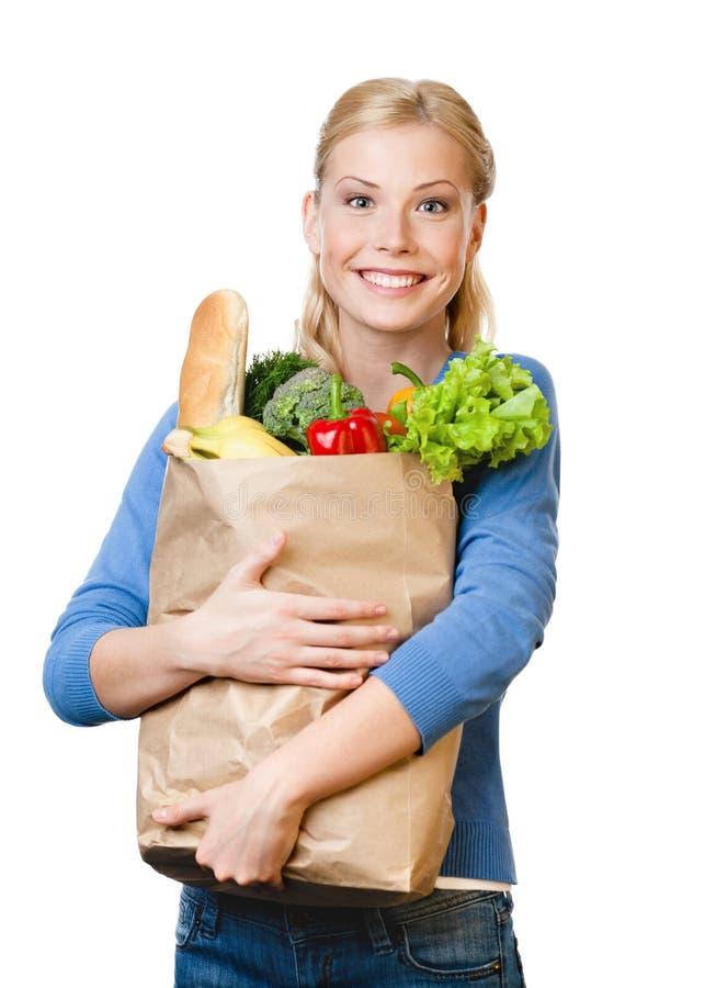 Mujer hermosa con un bolso lleno de consumición sana imagen de archivo