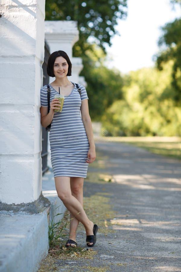 Mujer hermosa con un cóctel verde Una mujer bonita que se inclina en una pared en un fondo natural Concepto casual de la moda imagen de archivo