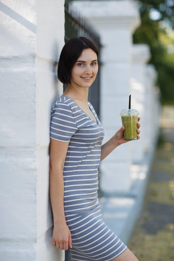 Mujer hermosa con un cóctel verde Una mujer bonita que se inclina en una pared en un fondo natural Concepto casual de la moda imágenes de archivo libres de regalías