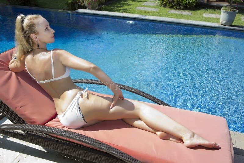 Mujer hermosa con con un pelo rubio largo, una figura delgada en un traje de baño del bikini sobre la piscina con agua azul brill imagenes de archivo