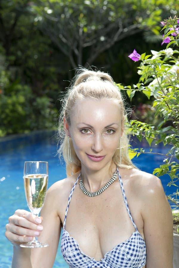 Mujer hermosa con con un pelo rubio largo, una figura delgada en un traje de baño del bikini sobre la piscina con agua azul brill fotografía de archivo