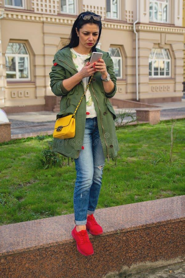 Mujer hermosa con un smartphone al aire libre fotos de archivo libres de regalías