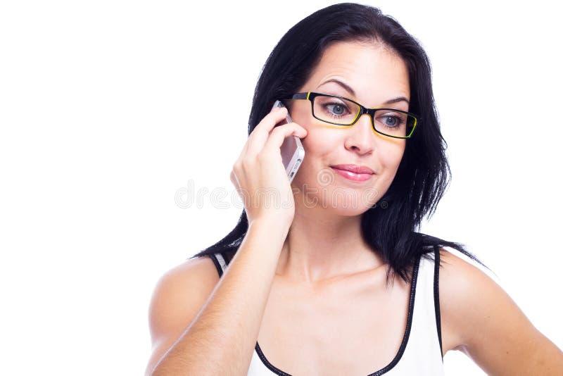 Mujer hermosa con un teléfono celular aislado en el fondo blanco fotografía de archivo