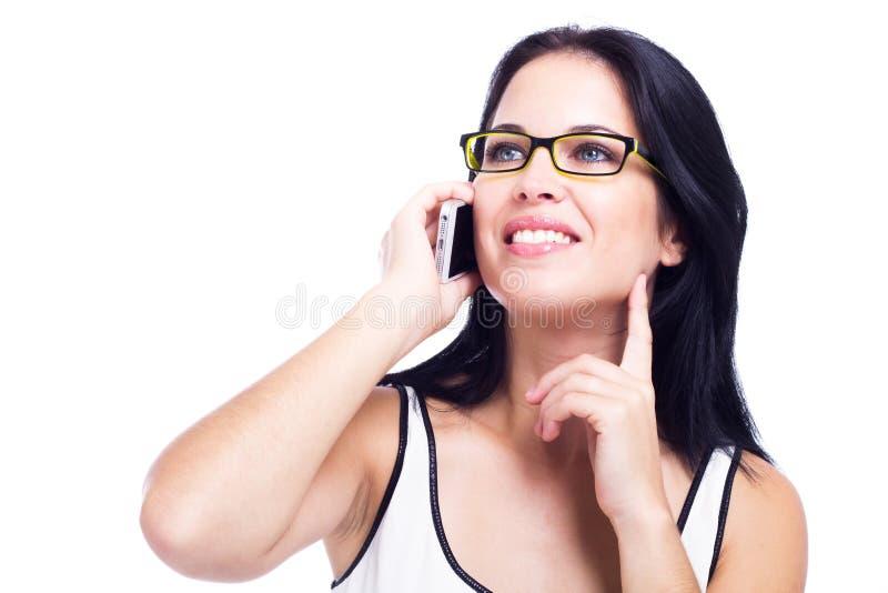 Mujer hermosa con un teléfono celular aislado en el fondo blanco foto de archivo