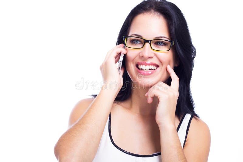 Mujer hermosa con un teléfono celular aislado en el fondo blanco fotografía de archivo libre de regalías