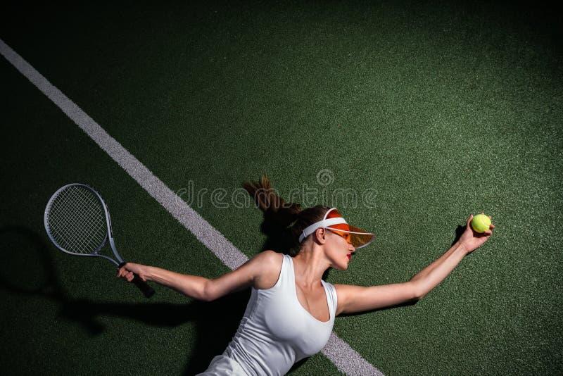 Mujer hermosa con una estafa que juega a tenis fotografía de archivo
