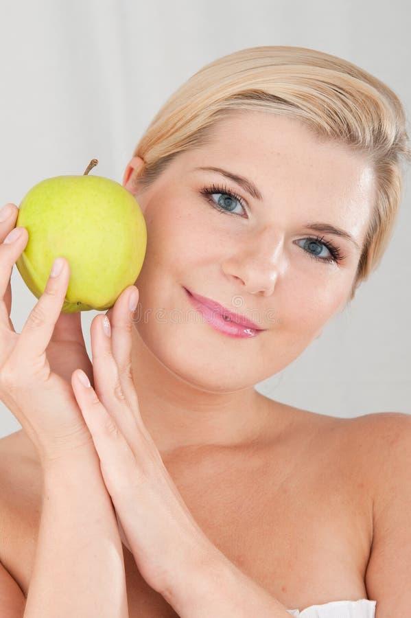 Mujer hermosa con una piel y una manzana sanas fotos de archivo