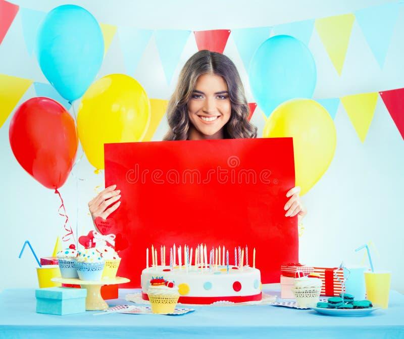 Mujer hermosa con una torta de cumpleaños que hace gesto del silencio imágenes de archivo libres de regalías
