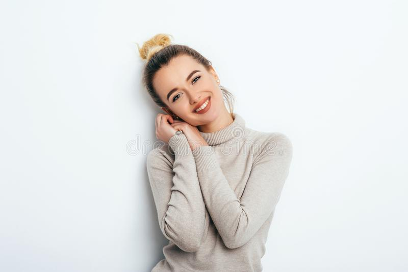 Mujer hermosa contenta con la mirada del placer del suéter del bollo del pelo que lleva que se coloca sobre la pared blanca mient imagen de archivo libre de regalías