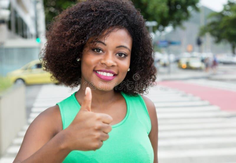 Mujer hermosa de África en una camisa verde que muestra el pulgar para arriba adentro fotos de archivo