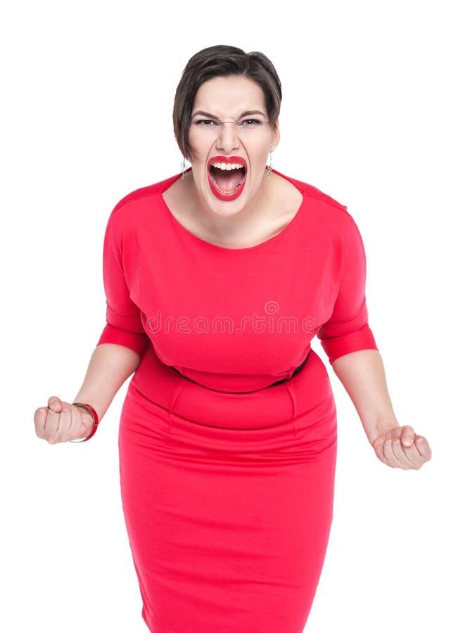 Mujer hermosa de griterío enojada del tamaño extra grande en el vestido rojo aislado foto de archivo