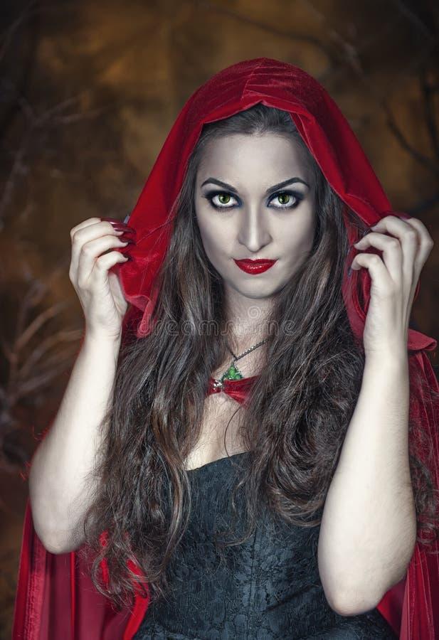Mujer hermosa de Halloween en capa roja fotografía de archivo libre de regalías
