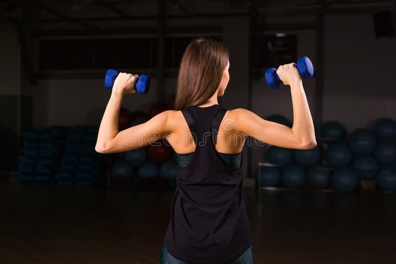 Mujer hermosa de la aptitud con pesas de gimnasia de elevación Mujer deportiva que levanta pesos ligeros Muchacha apta que ejerci imagenes de archivo