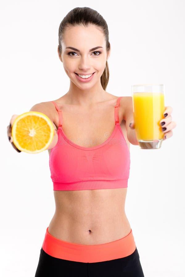 Mujer hermosa de la aptitud que da un jugo y una mitad de la naranja foto de archivo