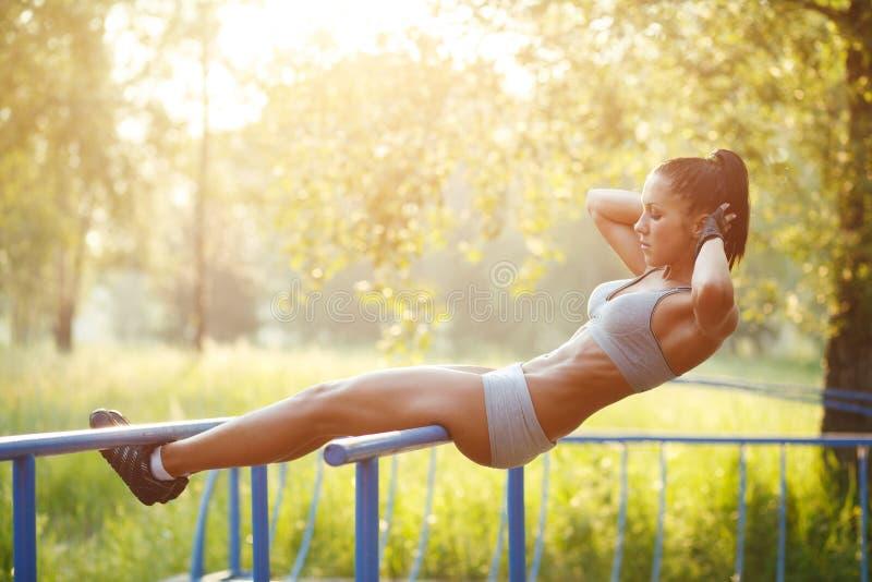 Mujer hermosa de la aptitud que hace ejercicio en al aire libre soleado de las barras fotos de archivo