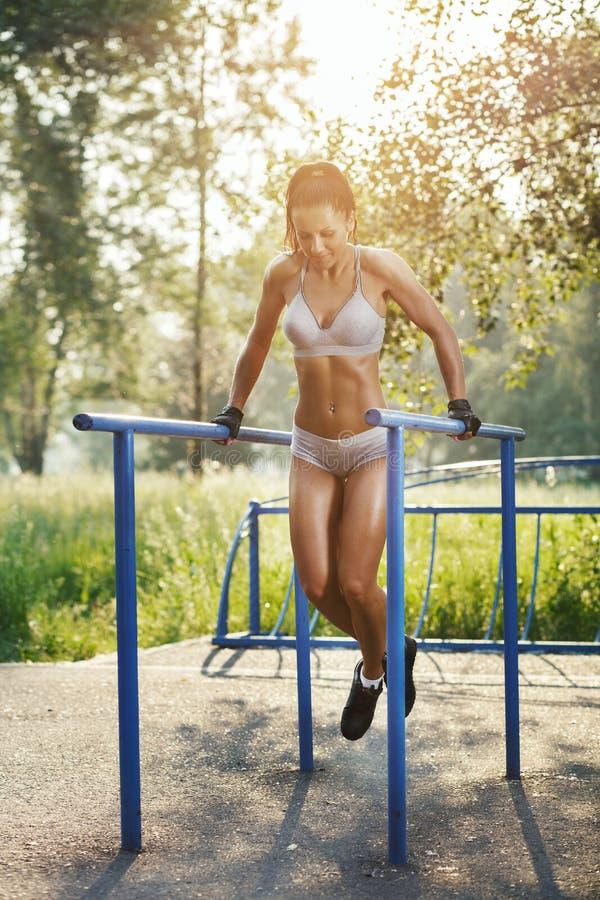 Mujer hermosa de la aptitud que hace ejercicio en al aire libre soleado de las barrases paralelas imagen de archivo libre de regalías