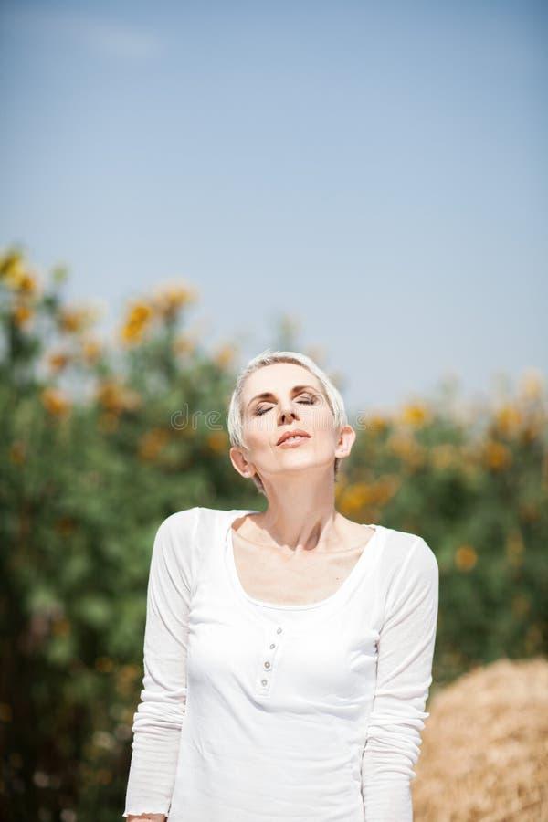 Mujer hermosa de la Edad Media en una escena rural del campo al aire libre con los girasoles foto de archivo libre de regalías