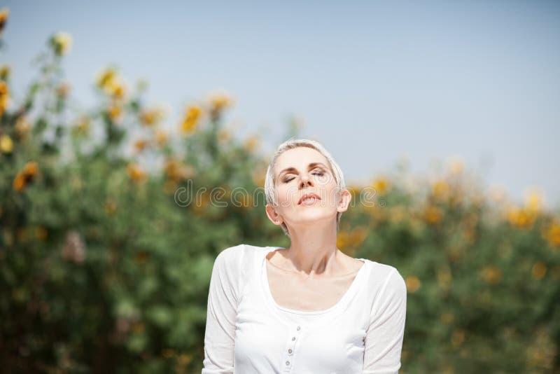 Mujer hermosa de la Edad Media en una escena rural del campo al aire libre con los girasoles imágenes de archivo libres de regalías