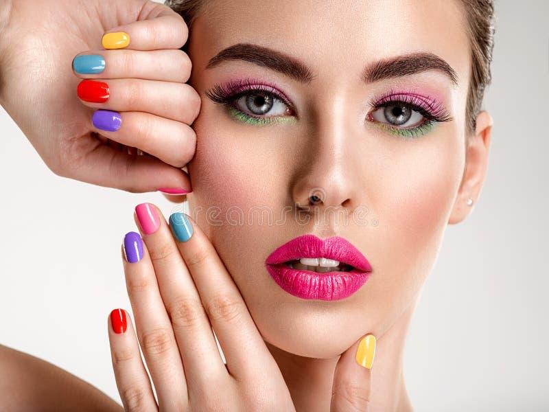 Mujer hermosa de la moda con clavos coloreados Muchacha blanca atractiva con la manicura multicolora imagenes de archivo