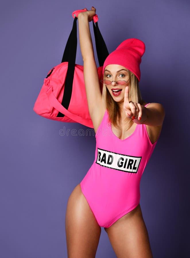 Mujer hermosa de la moda con el bolso rosado grande del deporte en el sombrero que presenta en púrpura fotografía de archivo