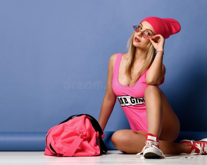 Mujer hermosa de la moda con el bolso rosado grande del deporte en el sombrero que presenta en púrpura foto de archivo libre de regalías