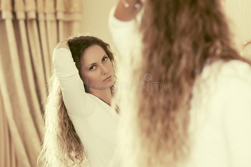 Mujer hermosa de la moda con los pelos rizados largos que miran en el espejo fotografía de archivo libre de regalías