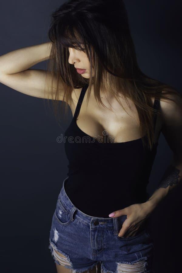 Mujer hermosa de la moda que lleva un top sin mangas negro imagen de archivo libre de regalías