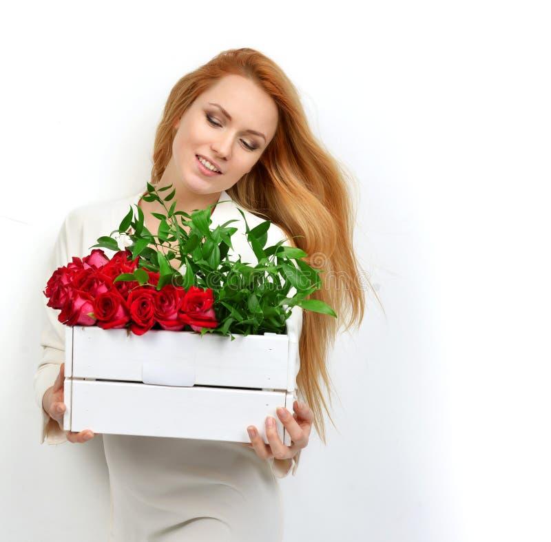 Mujer hermosa de la moda que se sienta con un ramo de rosas en prett fotografía de archivo