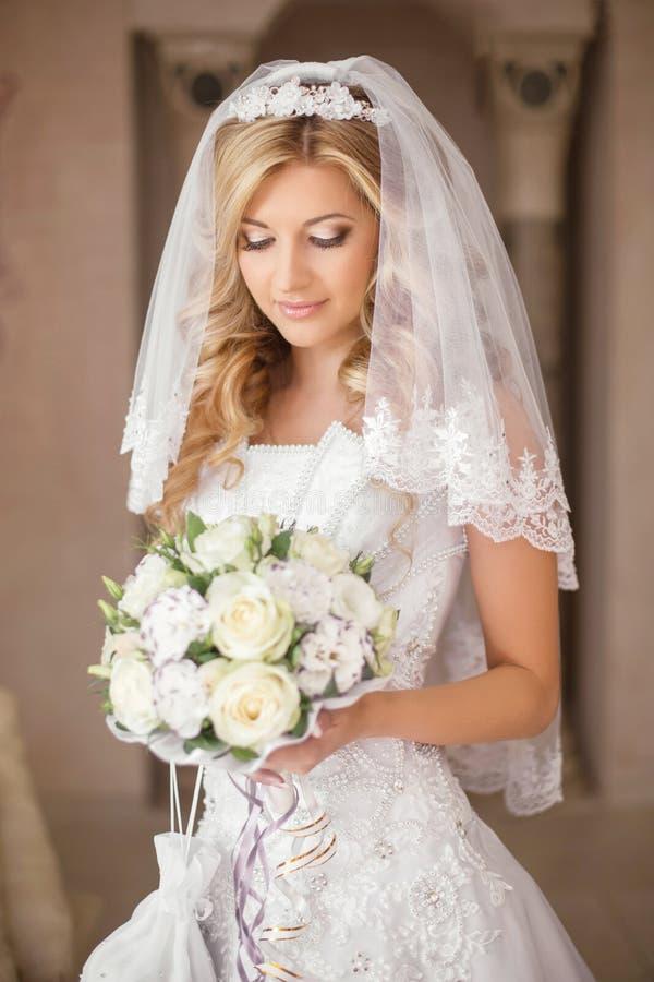 Mujer hermosa de la novia con el ramo de flores, casandose el maquillaje fotos de archivo