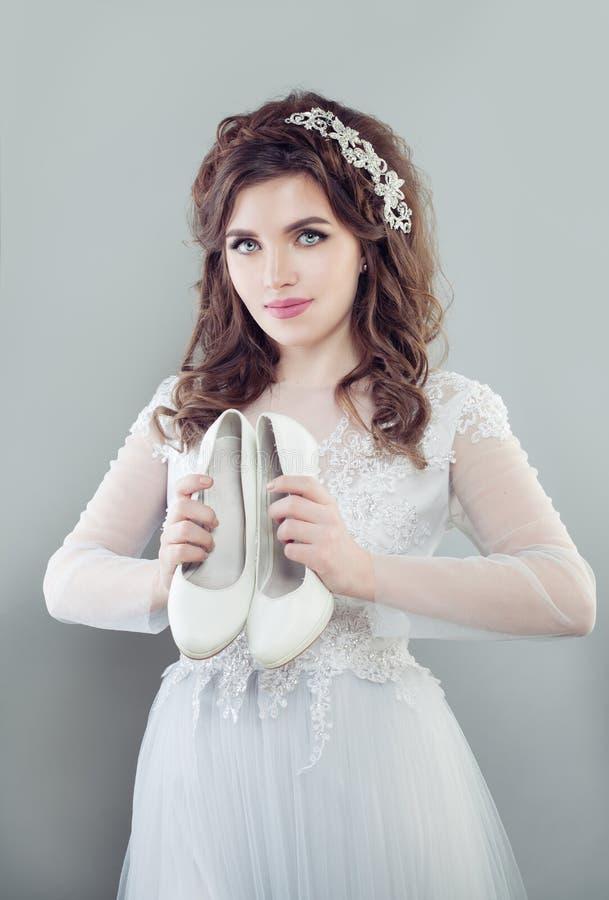 Mujer hermosa de la novia que sostiene los zapatos nupciales blancos imágenes de archivo libres de regalías